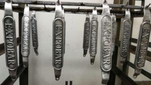 Placa Expobar en aluminio pintado en epoxi negro, cintado y lacado mate